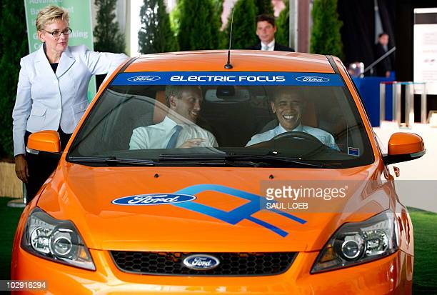 US President Barack Obama sits in an electric Ford Focus alongside Holland Michigan Mayor Kurt Dykstra and Michigan Governor Jennifer Granholm...