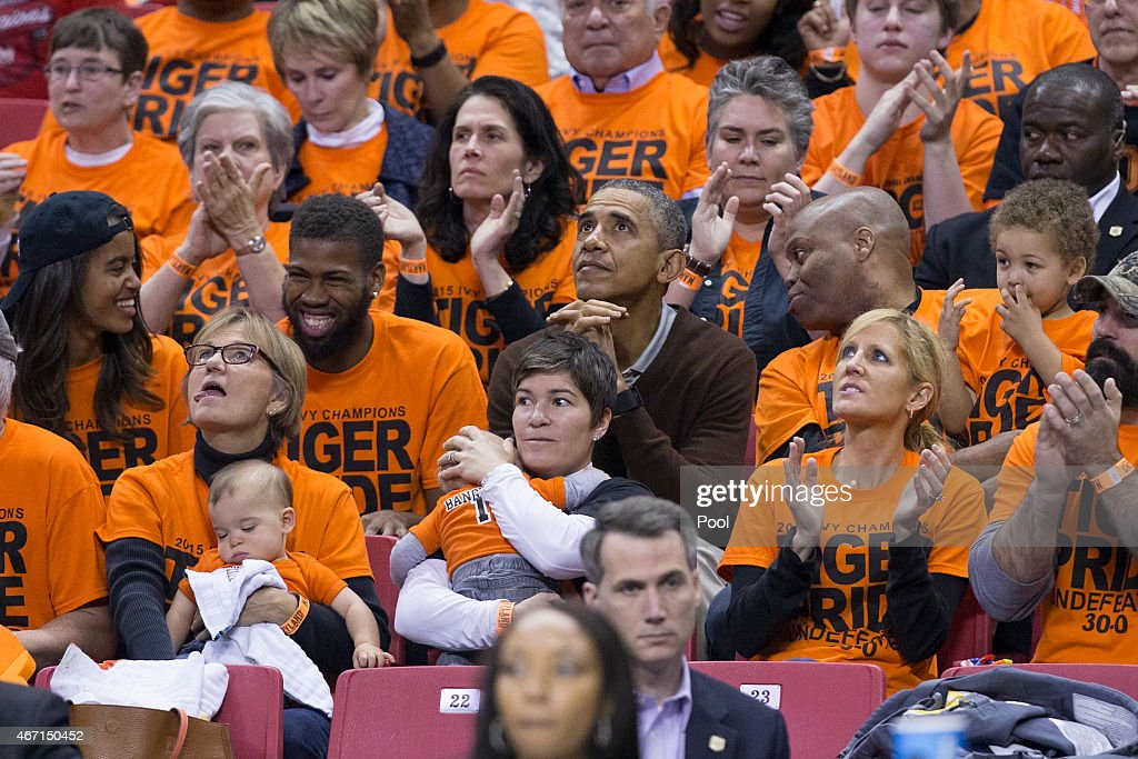 President Barack Obama sits with his brotherinlaw Craig Robinson his nephew Avery Robinson and daughter Malia while attending the Green Bay versus...