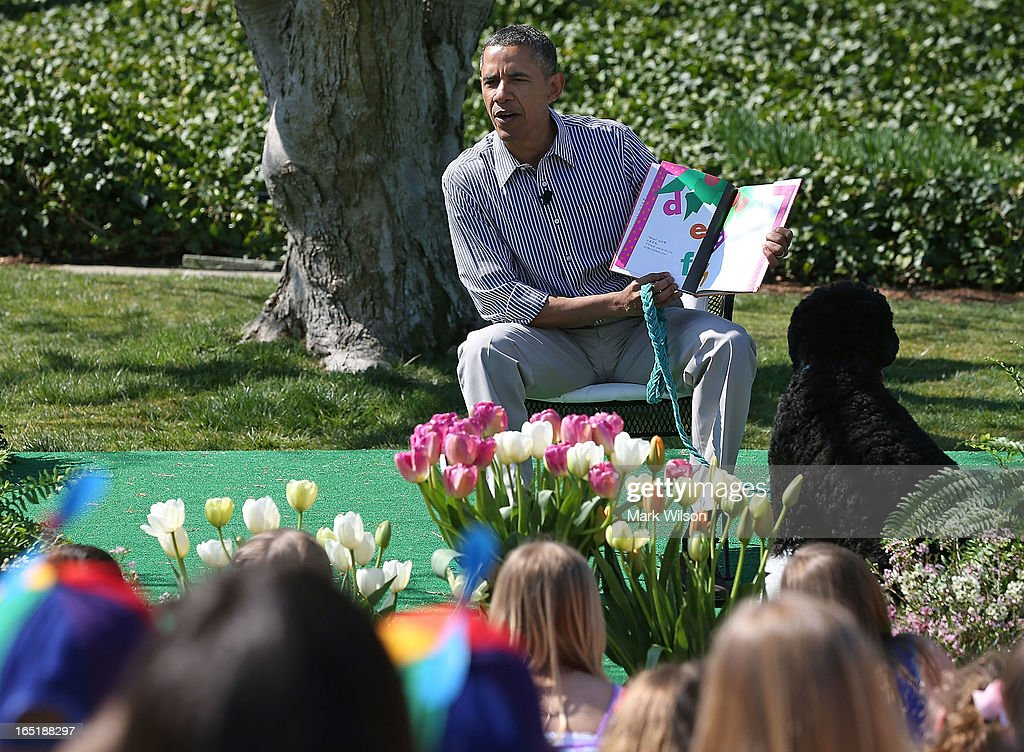 U.S. President Barack Obama sits with his dog Bo and reads a book to children during the annual Easter Egg Roll on the White House tennis court April 1, 2013 in Washington, DC. Thousands of people are expected to attend the 134-year-old tradition of rolling colored eggs down the White House lawn that was started by President Rutherford B. Hayes in 1878.