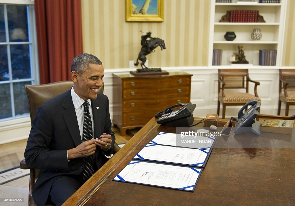 US President Barack Obama smiles after signing H.R. 2747: Streamlining Claims Processing for Federal Contractor Employees Act, and S. 893: Veterans Compensation Cost-of-Living Adjustment Act of 2013, in the Oval Office of the White House on November 21, 2013 in Washington, DC. AFP PHOTO/Mandel NGAN