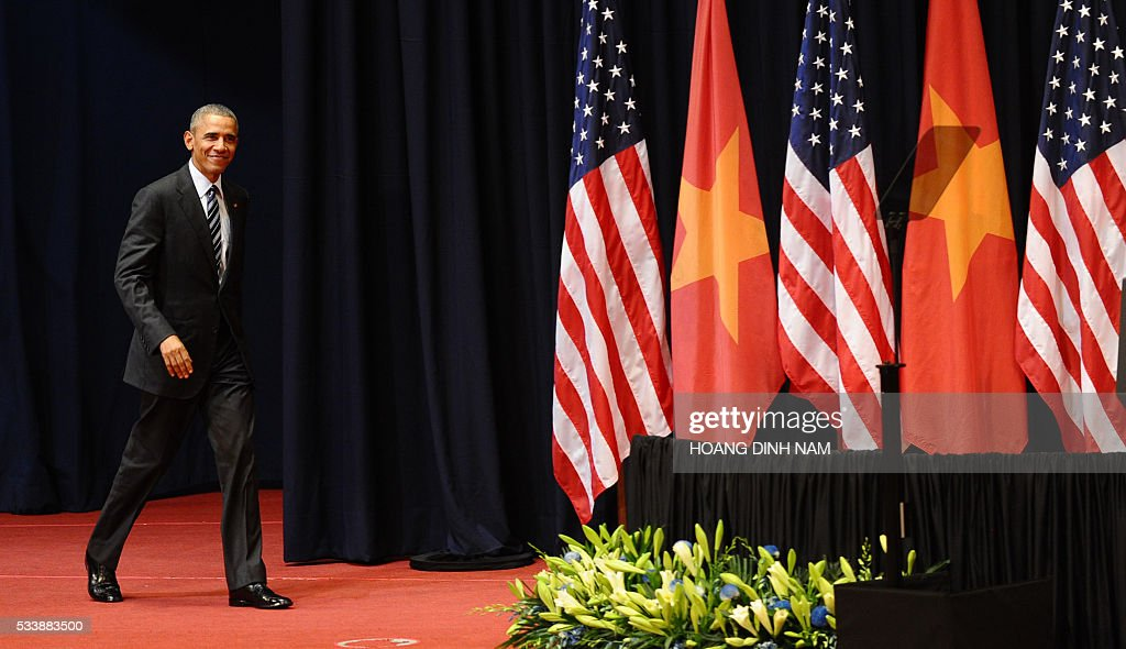 US President Barack Obama smiles as he arrives to give a speech at the National Convention Center in Hanoi on May 24, 2016. Obama, currently on a visit to Vietnam, met with civil society leaders including some of the country's long-harassed critics on May 24. / AFP / POOL / HOANG