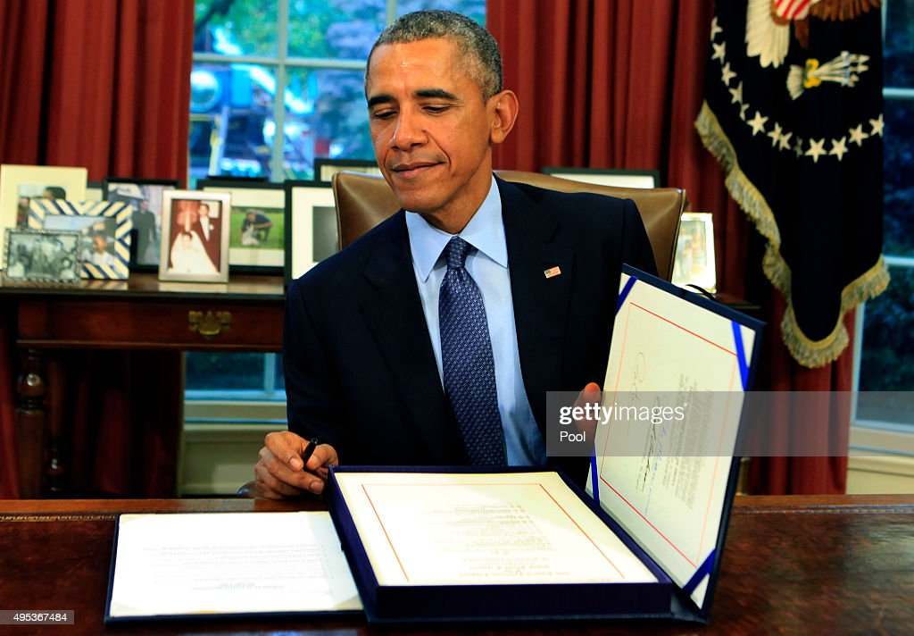 U.S. President Barack Obama smiles as he closes the legislative folder after he signed the bipartisan budget bill 2015 into law in the Oval Office of the White House November 2, 2015 in Washington, DC. Obama is traveling to New Jersey where he will talk about criminal justice reform and re-entry for formerly jailed people and he will later travel to New York for Democratic fund raisers.