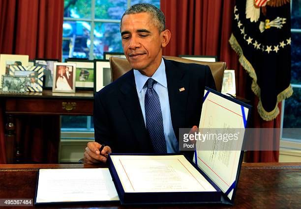 US President Barack Obama smiles as he closes the legislative folder after he signed the bipartisan budget bill 2015 into law in the Oval Office of...