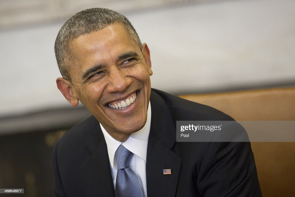 US President Barack Obama smiles as he meets with French President Francois Hollande in the Oval Office at the White House on February 11 2014 in...