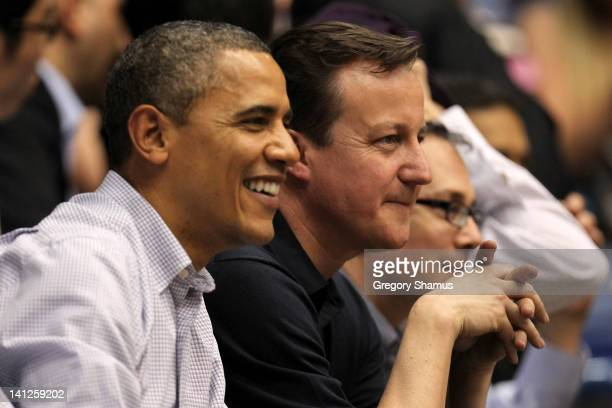 S President Barack Obama smiles as he sits with British Prime Minister David Cameron at UD Arena to watch the Western Kentucky Hilltoppers take on...