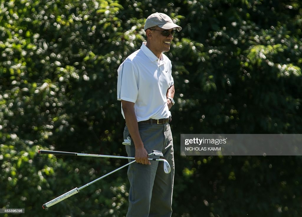 US President Barack Obama smiles as he watches his golfing partners putt on the first green while playing at the Farm Neck Golf Club at Martha's Vineyard, Massachusetts, on August 9, 2014, on the first day of the president's yearly summer vacation on the island. AFP PHOTO/Nicholas KAMM