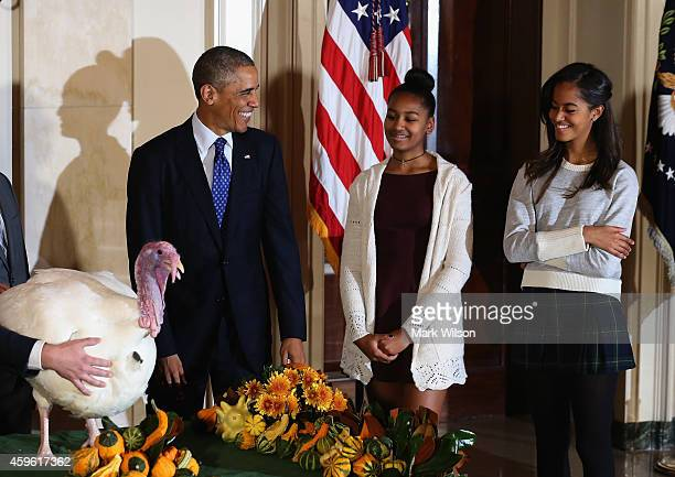 US President Barack Obama smiles at his his daughters Sasha and Malia after he pardoned 'Cheese' and his alternate Mac both 20week old 48pound...