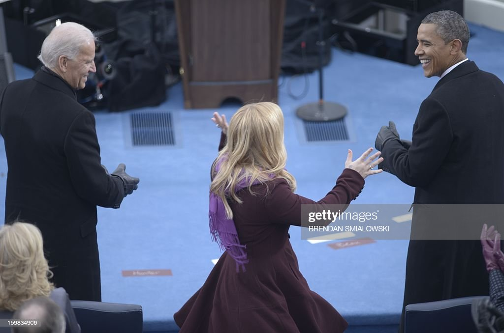 US President Barack Obama (R) smiles at singer Kelly Clarkson (C) as Vicer President Joe Biden (L) looks on after Obama took the oath of office during the 57th Presidential Inauguration ceremonial swearing-in at the US Capitol on January 21, 2013 in Washington, DC. The oath was administered by US Supreme Court Chief Justice John Roberts. AFP PHOTO/Brendan SMIALOWSKI