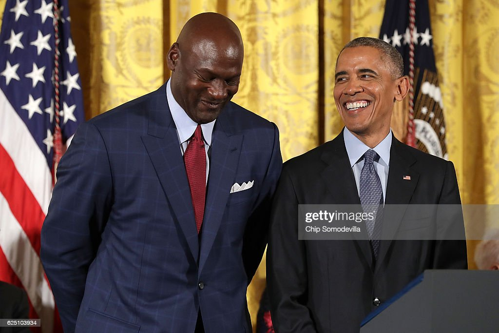 U.S. President Barack Obama smiles up at National Basketball Association Hall of Fame member and legendary athlete Michael Jordan before awarding him with the Presidential Medal of Freedom during a ceremony in the East Room of the White House November 22, 2016 in Washington, DC. Obama presented the medal to 19 living and two posthumous pioneers in science, sports, public service, human rights, politics and the arts.