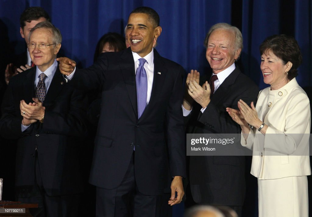 S President Barack Obama smiles while flanked by Senate Majority Leader Harry Reid Sen Joe Lieberman and Sen Susan Collins during a bill signing...