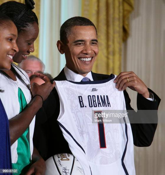 S President Barack Obama smiles while receiving a jersey from the NCAA champion University of Connecticut women's basketball team in the East Room at...
