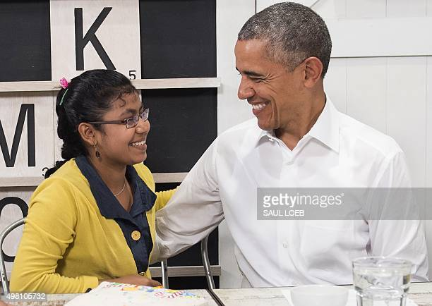 US President Barack Obama smiles with a 16yearold refugee girl from Myanmar that was subjected to human trafficking and will now be moving to the...