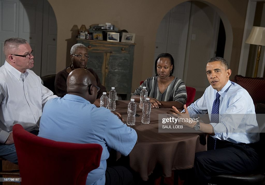 US President <a gi-track='captionPersonalityLinkClicked' href=/galleries/search?phrase=Barack+Obama&family=editorial&specificpeople=203260 ng-click='$event.stopPropagation()'>Barack Obama</a> (R) speaks about extending middle class tax cuts and the fiscal cliff alongside Tiffany Santana (2nd R), Richard Santana (L), Velma Massenburg (2nd L) and Jimmie Massenburg (C) at their home in Falls Church, Virginia, on December 6, 2012. Tiffany Santana, a high school English teacher, had previously contacted Obama about how an increase in her taxes would affect her family. AFP PHOTO / Saul LOEB