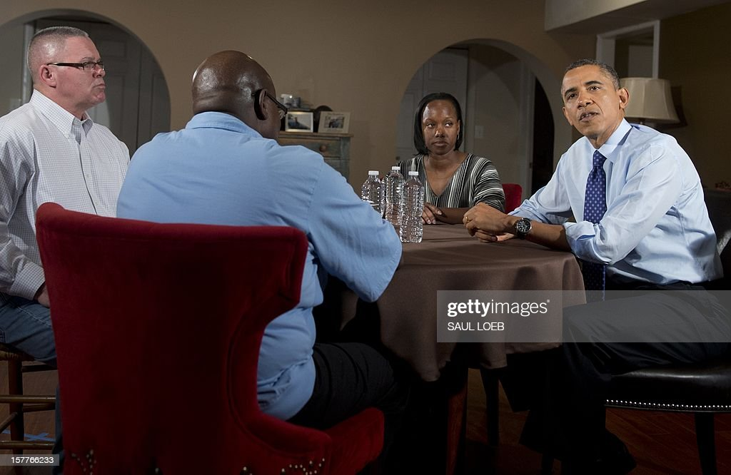 US President Barack Obama (R) speaks about extending middle class tax cuts and the fiscal cliff alongside Tiffany Santana (2nd R), Richard Santana (L), and Jimmie Massenburg (2nd L) at their home in Falls Church, Virginia, on December 6, 2012. Tiffany Santana, a high school English teacher, had previously contacted Obama about how an increase in her taxes would affect her family. AFP PHOTO / Saul LOEB