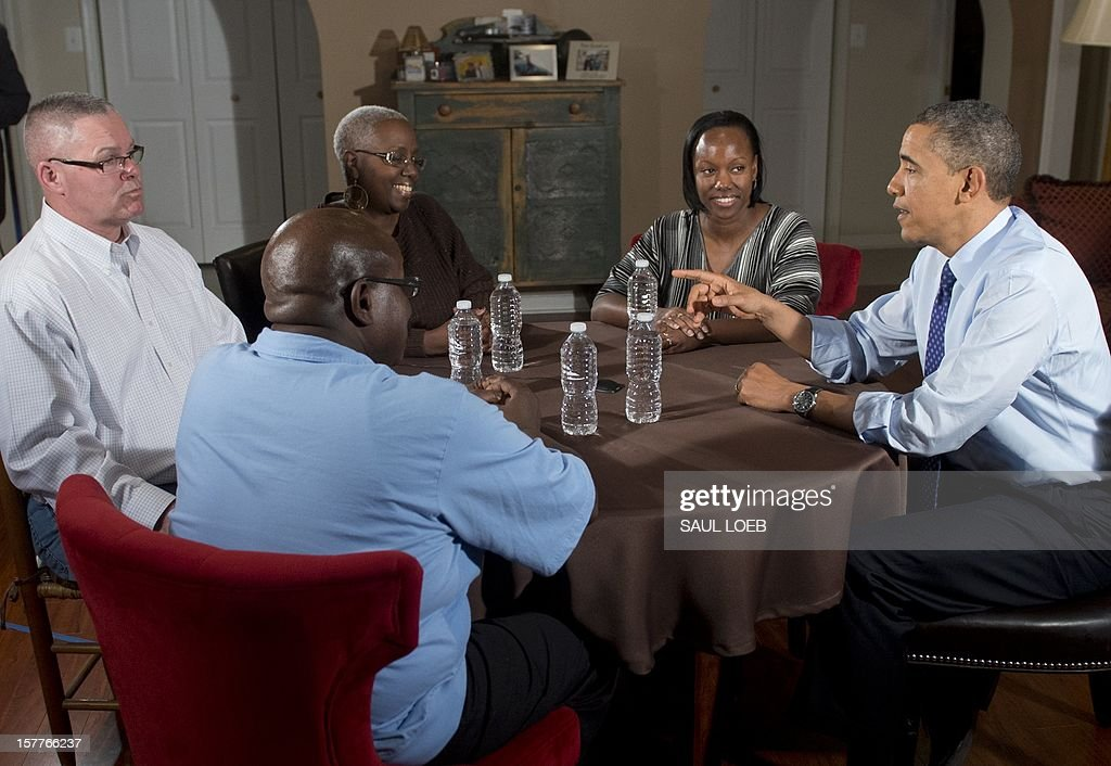 US President Barack Obama (R) speaks about extending middle class tax cuts and the fiscal cliff alongside Tiffany Santana (2nd R), Richard Santana (L), Velma Massenburg (2nd L) and Jimmie Massenburg (C) at their home in Falls Church, Virginia, on December 6, 2012. Tiffany Santana, a high school English teacher, had previously contacted Obama about how an increase in her taxes would affect her family. AFP PHOTO / Saul LOEB