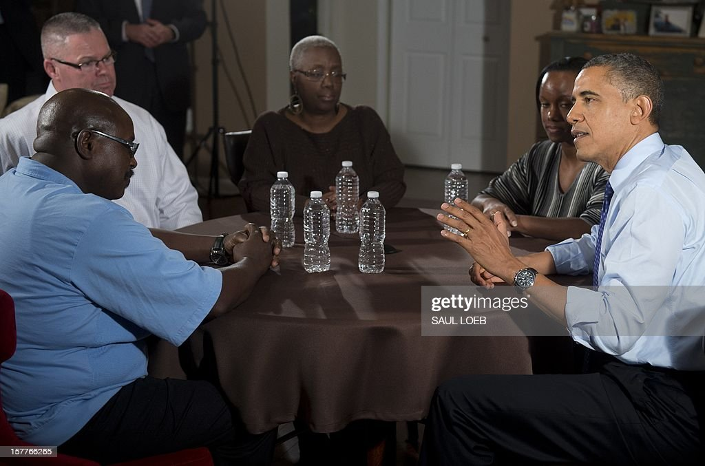 US President Barack Obama (R) speaks about extending middle class tax cuts and the fiscal cliff alongside Tiffany Santana (2nd R), Richard Santana (top L), Velma Massenburg (C) and Jimmie Massenburg (bottom L) at their home in Falls Church, Virginia, on December 6, 2012. Tiffany Santana, a high school English teacher, had previously contacted Obama about how an increase in her taxes would affect her family. AFP PHOTO / Saul LOEB