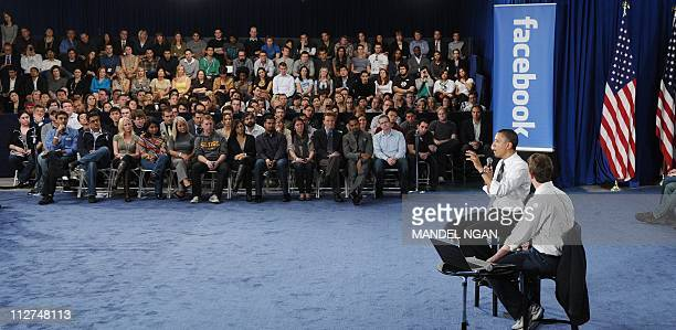US President Barack Obama speaks as Facebook CEO Mark Zuckerberg looks on during a town hall meeting April 20 2011 at Facebook headquarters in Palo...