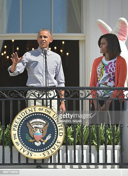 US President Barack Obama speaks as First Lady Michelle Obama looks on during the annual Easter egg roll on the South Lawn of the White House on...