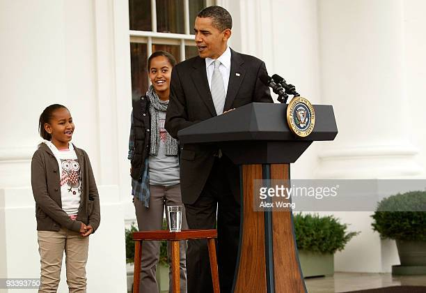 S President Barack Obama speaks as his daughters Sasha and Malia listen during an event to pardon a turkey named 'Courage' at the North Portico of...
