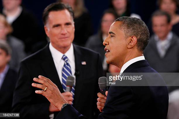 S President Barack Obama speaks as Republican presidential candidate Mitt Romney listens during a town hall style debate at Hofstra University...