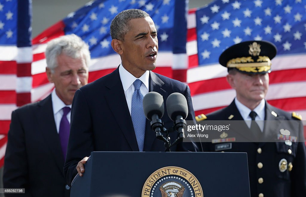 U.S. President <a gi-track='captionPersonalityLinkClicked' href=/galleries/search?phrase=Barack+Obama&family=editorial&specificpeople=203260 ng-click='$event.stopPropagation()'>Barack Obama</a> (2nd L) speaks as Secretary of Defense <a gi-track='captionPersonalityLinkClicked' href=/galleries/search?phrase=Chuck+Hagel&family=editorial&specificpeople=504963 ng-click='$event.stopPropagation()'>Chuck Hagel</a> (L) and Chairman of the Joint Chiefs Gen. <a gi-track='captionPersonalityLinkClicked' href=/galleries/search?phrase=Martin+Dempsey&family=editorial&specificpeople=2116621 ng-click='$event.stopPropagation()'>Martin Dempsey</a> (R) listen during a ceremony to mark the 13th anniversary of the 9/11 terrorists attacks at the Pentagon Memorial September 11, 2014 in front of the Pentagon in Arlington, Virginia. This year marks the 13th anniversary of the September 11th terrorist attacks that killed nearly 3,000 people at the World Trade Center, Pentagon and on Flight 93..