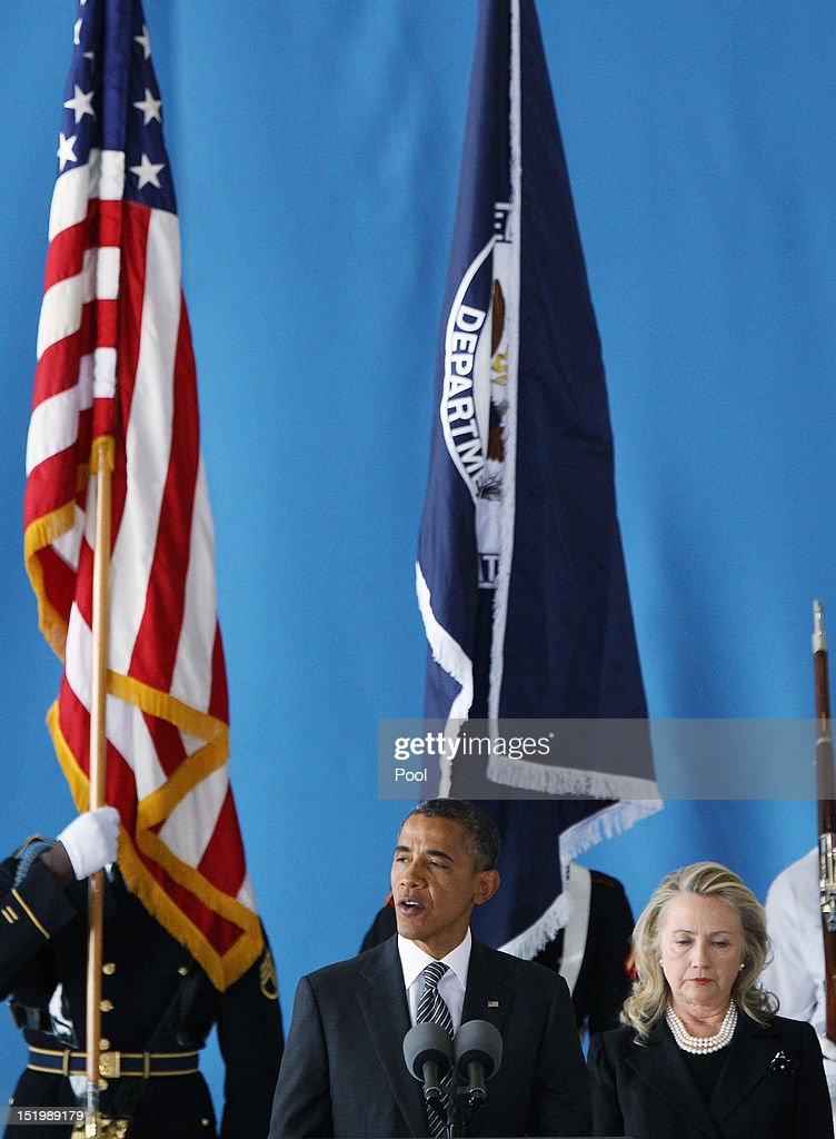 S President Barack Obama speaks as US Secretary of State Hillary Clinton listens during the Transfer of Remains Ceremony for the return of Ambassador...