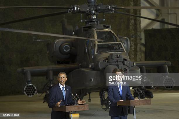 US President Barack Obama speaks next to Prime Minister Taavi Roivas of Estonia to US and Estonian members of the military at a hangar at Tallinn...