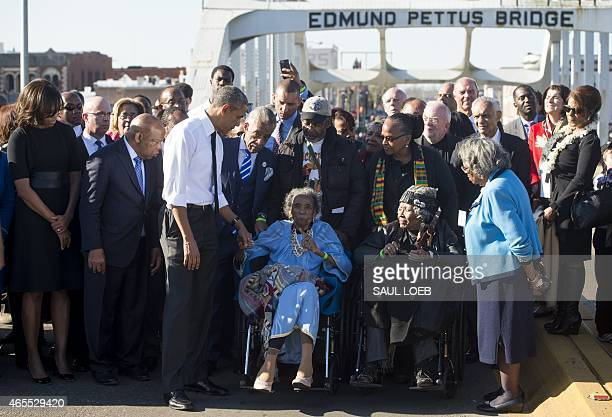 US President Barack Obama speaks to Amelia Boynton Robinson one of the original marchers alongside First Lady Michelle Obama and US Representative...