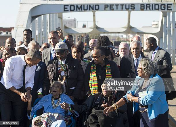 US President Barack Obama speaks to Amelia Boynton Robinson one of the original marchers after leading a walk across the Edmund Pettus Bridge to mark...