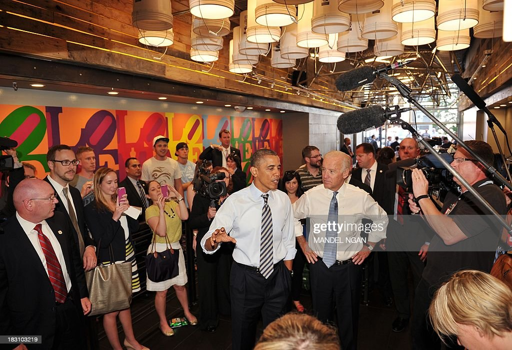 US President Barack Obama speaks to reporters as he and US Vice President Joe Biden (R) arrive to order lunch at Taylor Gourmet Deli on Pennsylvania Ave in Washington, DC on October 4, 2013. Mandel NGAN