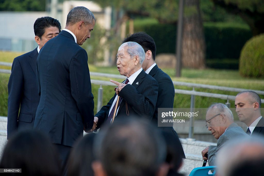 US President Barack Obama (2nd L) speaks to Sunao Tsuboi (C), a survivor of the 1945 atomic bombing of Hiroshima, as Japan's Prime Minister Shinzo Abe (back L) looks on, during a visit to the Hiroshima Peace Memorial Park on May 27, 2016. Obama on May 27 paid moving tribute to victims of the world's first nuclear attack. WATSON