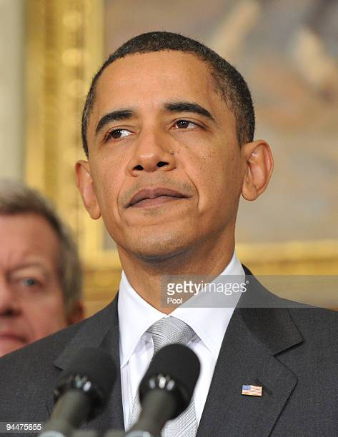President Barack Obama speaks to the press as Sen Max Baucus listens in the Roosevelt Room in the Eisenhower Executive Office Building on December 15...