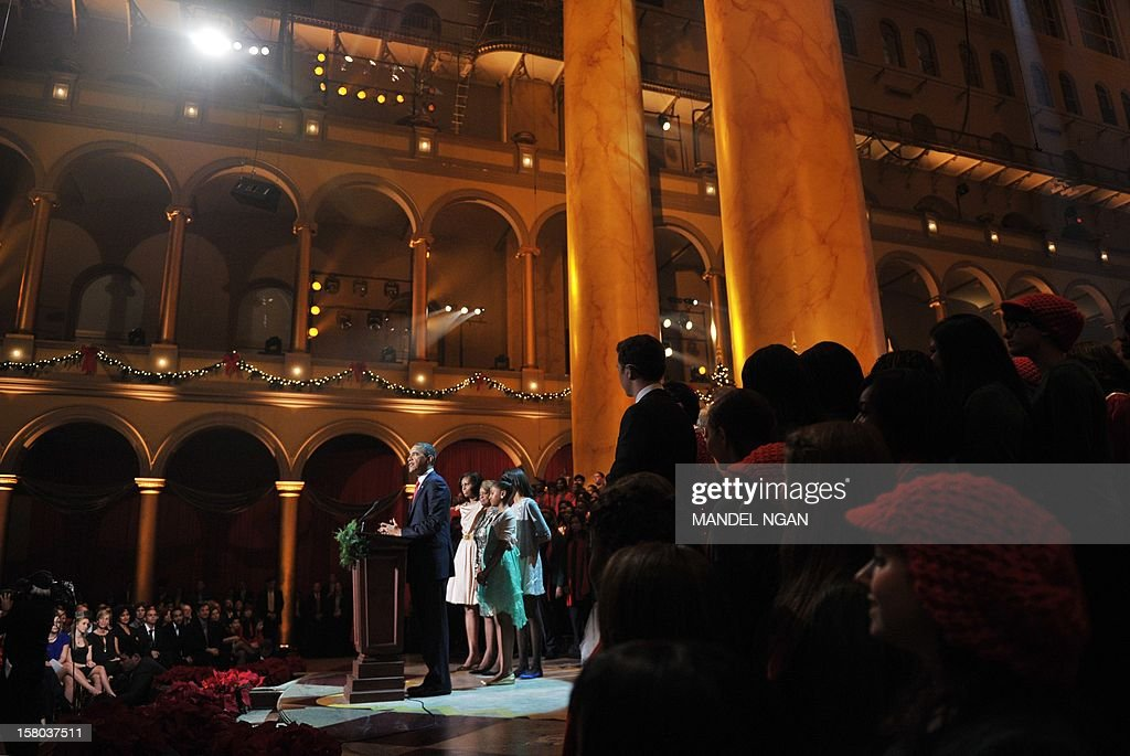 US President Barack Obama speaks watched by (from left) First Lady Michelle Obama, mother-in-law Marian Robinson, daughters Sasha and Malia during the taping of the 'Christmas in Washington' television special on December 9, 2012 at the Building Museum in Washington, DC. AFP PHOTO/Mandel NGAN