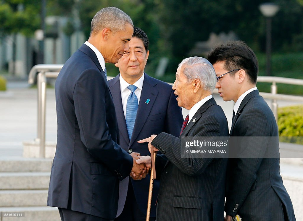 US Presdent Barack Obama (L) speaks with 91-year-old Sunao Tsuboi (2nd R), a survivor of the 1945 atomic bombing of Hiroshima, as Japanese Prime Minister Shinzo Abe (2nd L) listens during a visit to the Hiroshima Peace Memorial Park on May 27, 2016. Obama on May 27 paid moving tribute to victims of the world's first nuclear attack. / AFP / POOL / KIMIMASA