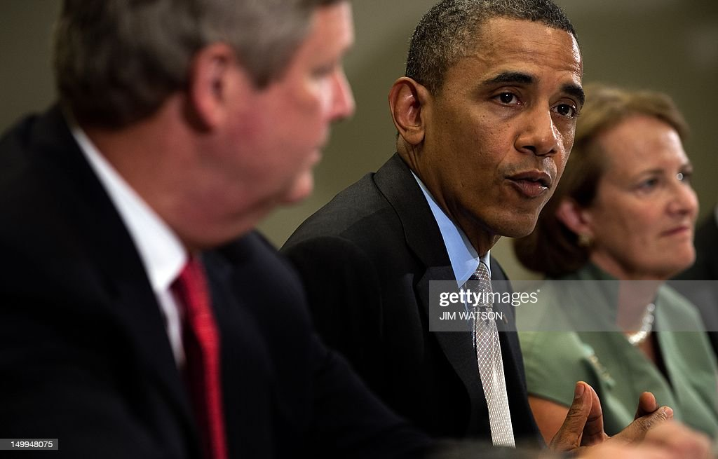 US President Barack Obama (C) speaks with Agriculture Secretary Tom Vilsack (L) and Administrator of the Small Business Administration Karen Mills (R) during a meeting with the White House Rural Council at the White House in Washington on August 7, 2012. AFP PHOTO/Jim WATSON