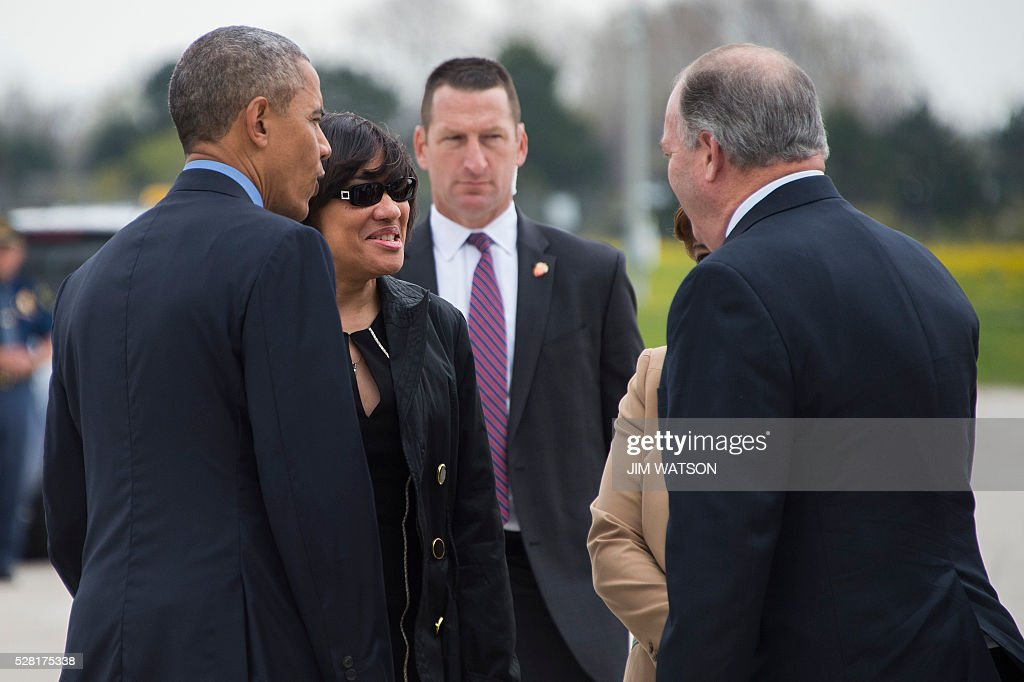 US President Barack Obama (L) speaks with Flint Mayor Karen Weaver (2nd L) upon his arrival at Bishop International Airport in Flint, Michigan, May 4, 2016. / AFP / Jim Watson