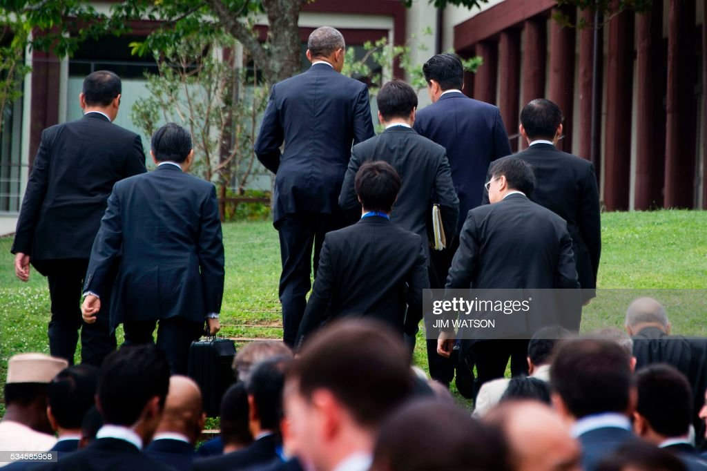 US President Barack Obama (top C) speaks with Japanese Prime Minister Shinzo Abe (top-2nd R) as they depart after taking part in the 'Outreach Session' family photo with world leaders at the G7 Summit in Shima in Mie prefecture on May 27, 2016. A British secession from the European Union in next month's referendum could have disastrous economic consequences, G7 leaders warned on May 27 at the close of the summit in Japan. / AFP / POOL / JIM