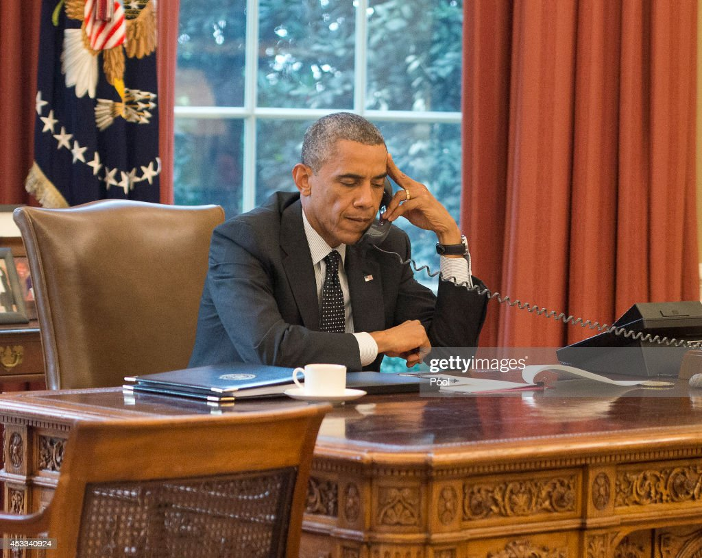 President Barack Obama speaks with King Abdullah II of the Hashemite Kingdom of Jordan on the phone from the Oval Office in the White House on August 8, 2014 in Washington DC. Obama had previously stated his concerns for the safety of Iraqi refugees on Mount Sinjar near Mosul and had approved 'targeted strikes' against ISIS convoys approaching the city of Erbil. The Saudi King had recently pledged to help displaced Iraqis and to take action against potential terrorists.