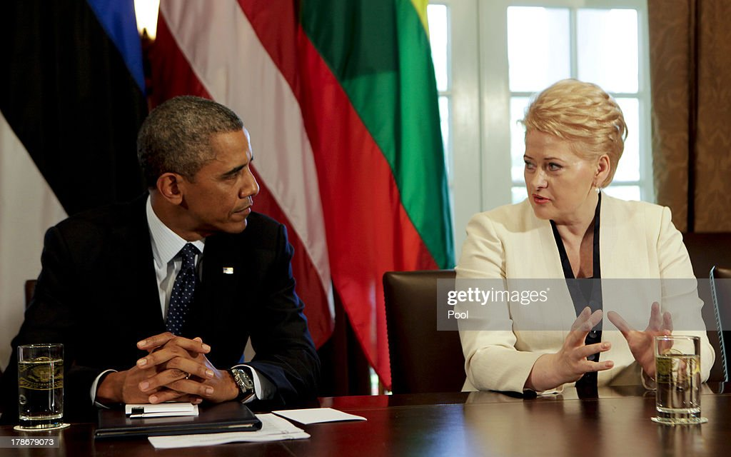 US President Barack Obama speaks with President Dalia Grybauskaite of Lithuania while in a meeting with President Andris Berzins of Latvia, and President Toomas Hendrik Ilves of Estonia (unseen) in the Cabinet Room of the White House August 30, 2013 in Washington, DC. A joint meeting was to be held that will highlight the transformations the Baltic States have undergone since restoring their independence two decades ago. President Obama spoke with the media about the ongoing situation in Syria.