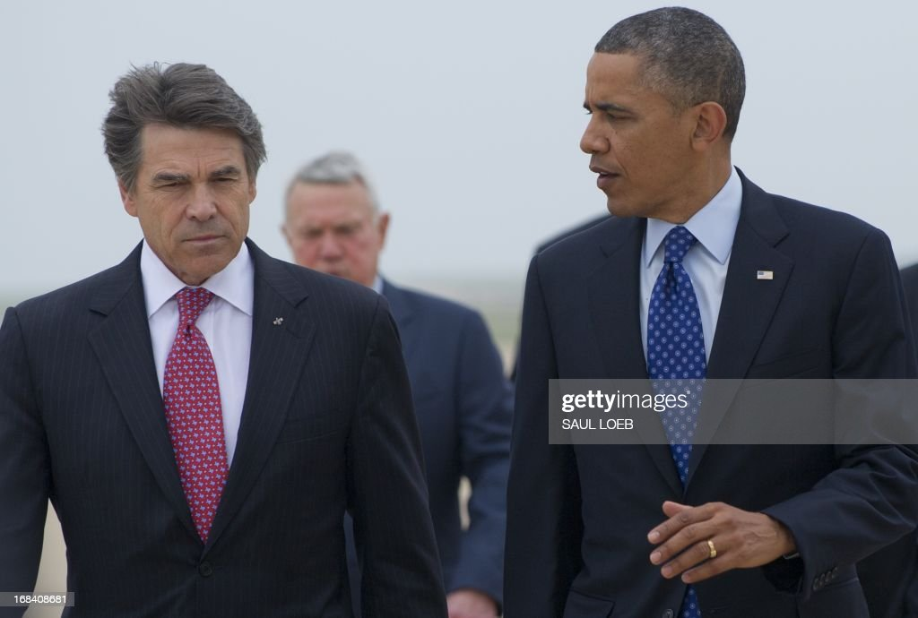 US President Barack Obama speaks with Texas Governor Rick Perry (L) after arriving on Air Force One at Austin-Bergstrom International Airport in Austin, Texas, May 9, 2013. Obama will speak on the economy and job creation. AFP PHOTO / Saul LOEB