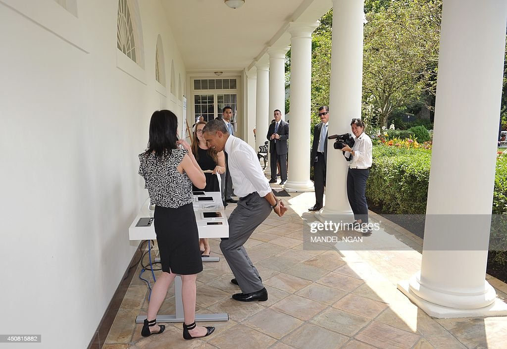 US President Barack Obama squats while looking at an adjustable height desk with Jen McCabe, who founded a small urban factory in Las Vegas to serve makers, designers, and startups, while viewing Maker Faire projects on the South Lawn of the White House on June 18, 2014 in Washington, DC. AFP PHOTO/Mandel NGAN