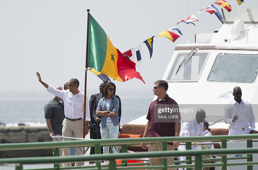 US President <a gi-track='captionPersonalityLinkClicked' href=/galleries/search?phrase=Barack+Obama&family=editorial&specificpeople=203260 ng-click='$event.stopPropagation()'>Barack Obama</a>, standing next to his daughter Malia, waves as he arrives by boat to tour Goree Island, including the House of Slaves, or Maison des Esclaves, off the coast of Dakar on June 27, 2013. Obama and his family toured the museum at the site where African slaves were held before going through the door and being shipped off the continent as slaves. AFP PHOTO / Saul LOEB