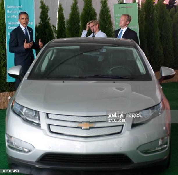 US President Barack Obama stands alongside an electric Chevrolet Volt and Holland Michigan Mayor Kurt Dykstra and Michigan Governor Jennifer Granholm...