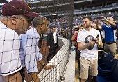 US President Barack Obama stands alongside Representative Dan Kildee Democrat of Michigan as he greets fans during the annual Congressional Baseball...
