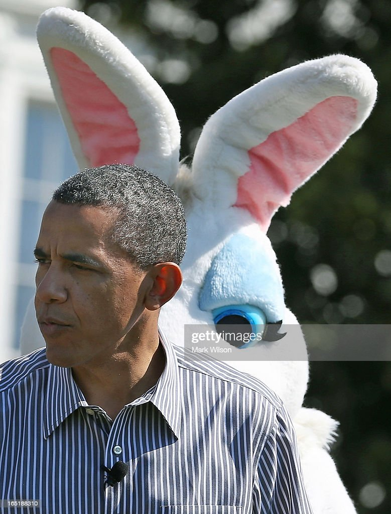 U.S. President Barack Obama stands in front of the Easter Bunny while he participates in the annual Easter Egg Roll on the White House tennis court April 1, 2013 in Washington, DC. Thousands of people are expected to attend the 134-year-old tradition of rolling colored eggs down the White House lawn that was started by President Rutherford B. Hayes in 1878.