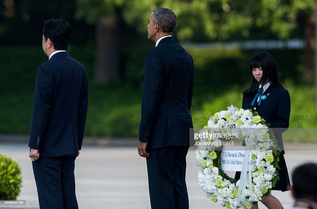 US President Barack Obama (C) stands next to Japanese Prime Minister Shinzo Abe (L) after laying a wreath at the Hiroshima Peace Memorial park cenotaph in Hiroshima on May 27, 2016. Obama became the first sitting US leader to visit the site that ushered in the age of nuclear conflict. / AFP / JOHANNES
