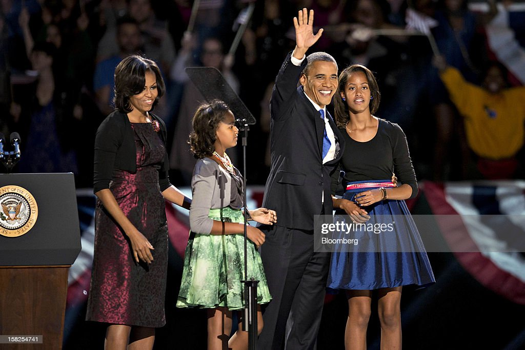 'BEST PHOTOS OF 2012' (): U.S. President Barack Obama stands on stage with his wife Michelle Obama, left, and daughters Sasha, second left, and Malia, right, before making an acceptance speech during an election night rally in Chicago, Illinois, U.S., in the early morning on Wednesday, Nov. 7, 2012. Obama, the post-partisan candidate of hope who became the first black U.S. president, won re-election today by overcoming four years of economic discontent with a mix of political populism and electoral math. Photographer: Daniel Acker/Bloomberg via Getty Images