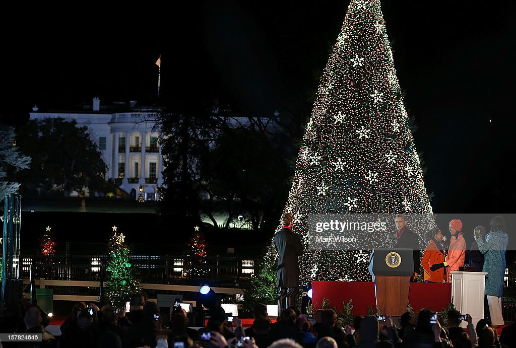 US President Barack Obama (C) stands with actor Neil Patrick Harris (L), Sasha and Malia Obama and first lady Michelle Obama and her mother Marion participate in the annual lighting of the National Christmas tree on December 6, 2012 in Washington, DC. This year is the 90th annual National Christmas Tree Lighting Ceremony.