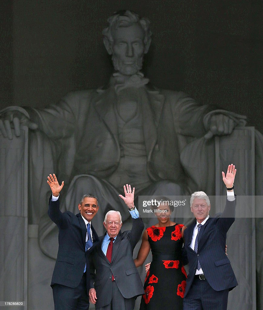 President Barack Obama (L) stands with his wife Michelle Obama (2nd-R) and former presidents Jimmy Carter (2nd-L) and Bill Clinton (R) during the ceremony to commemorate the 50th anniversary of the March on Washington for Jobs and Freedom August 28, 2013 in Washington, DC. It was 50 years ago today that Martin Luther King, Jr. delivered his 'I Have A Dream Speech' on the steps of the Lincoln Memorial.