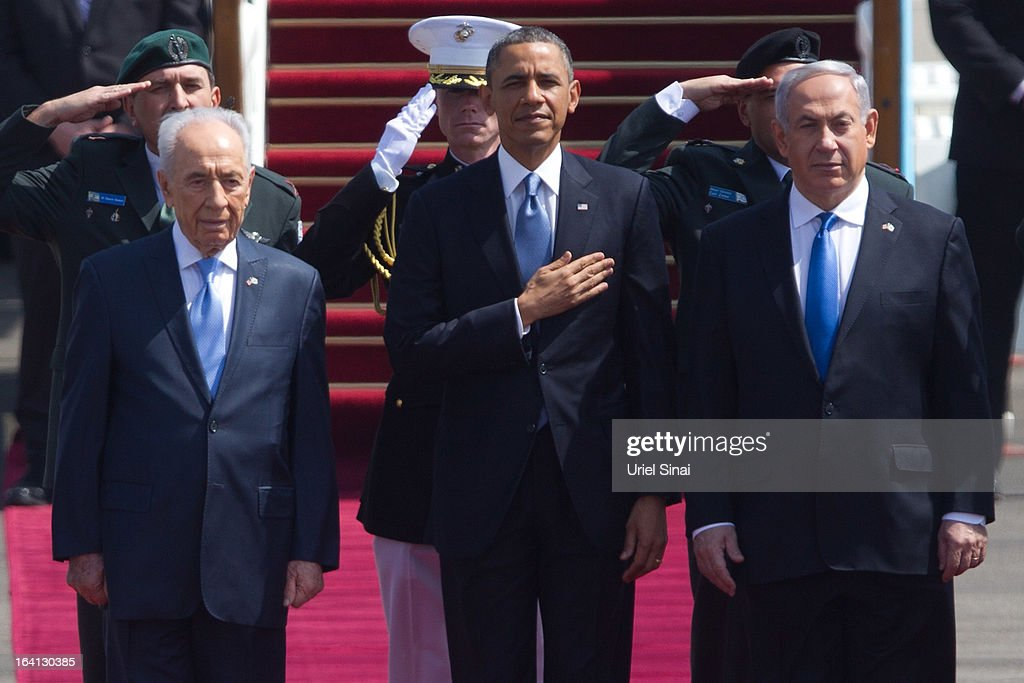 US President Barack Obama (C) stands with Israeli President Shimon Peres (L) and Israeli Prime Minister Benjamin Netanyahu (R) for the American national anthem during an official welcoming ceremony on his arrival at Ben Gurion International Airport on March, 20, 2013 near Tel Aviv, Israel. This will be Obama's first visit as President to the region, and his itinerary will include meetings with the Palestinian and Israeli leaders as well as a visit to the Church of the Nativity in Bethlehem.